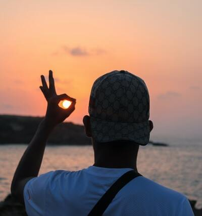 Un homme fait le signe ok au coucher du soleil